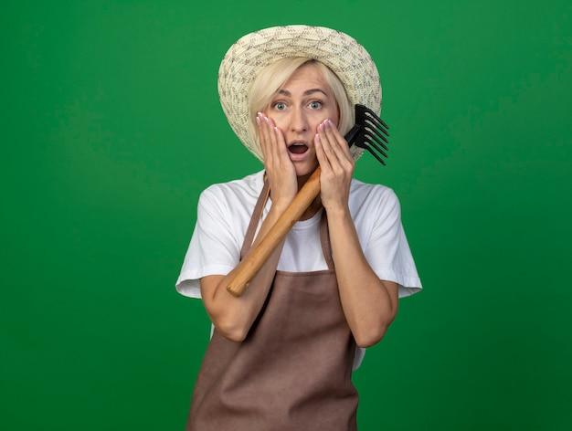 Überraschte blonde gärtnerin mittleren alters in uniform mit hut, die harke hält und die hände auf dem gesicht hält
