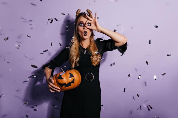 Überraschte blonde hexe, die unter konfetti steht. schockierte junge frau, die auf lila wand mit halloween-kürbis aufwirft.