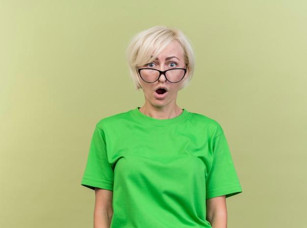 Überraschte blonde slawische frau mittleren alters, die brille betrachtet kamera betrachtet auf olivgrünem hintergrund mit kopienraum