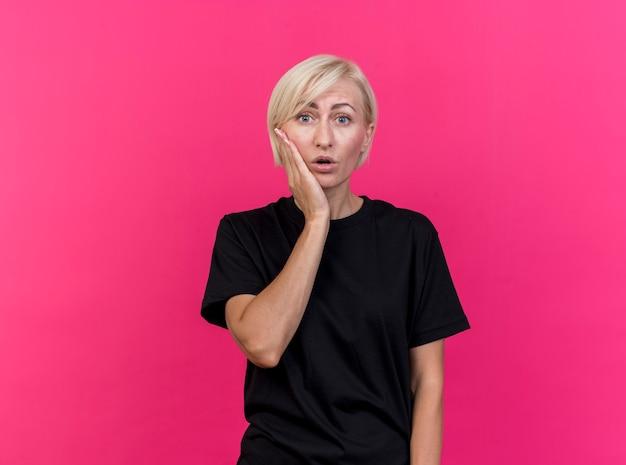 Überraschte blonde slawische frau mittleren alters, die hand auf wange hält, die kamera lokal auf purpurrotem hintergrund mit kopienraum betrachtet