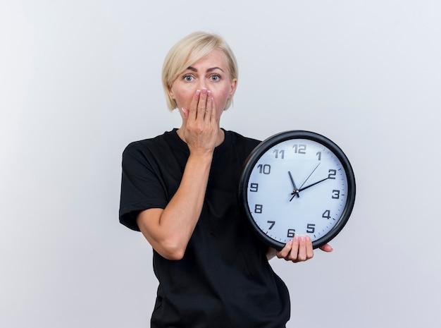 Überraschte blonde slawische frau mittleren alters, die uhr hält, die hand auf mund hält und kamera lokalisiert auf weißem hintergrund mit kopienraum betrachtet