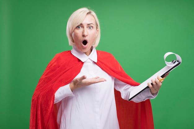 Überraschte blonde superheldin mittleren alters im roten umhang, die mit der hand auf die zwischenablage zeigt, die auf grüner wand isoliert ist