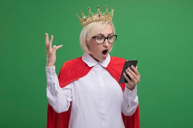 Überraschte blonde superheldin mittleren alters in rotem umhang mit brille und krone, die das handy hält und betrachtet, das die hand in der luft hält, isoliert auf grüner wand mit kopierraum