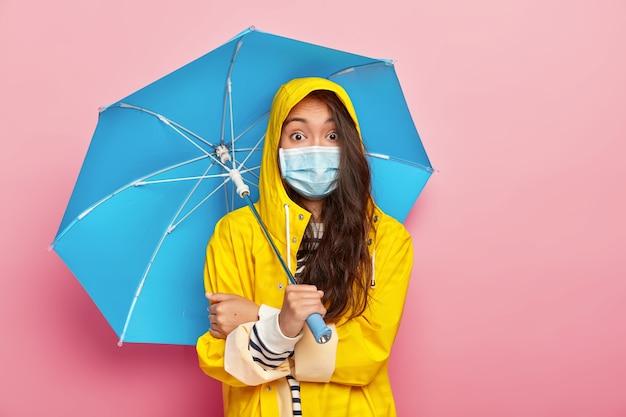 Überraschte brünette asiatische frau trägt medizinische maske, ist vor krankheiten geschützt, trägt gelben regenmantel, hält regenschirm