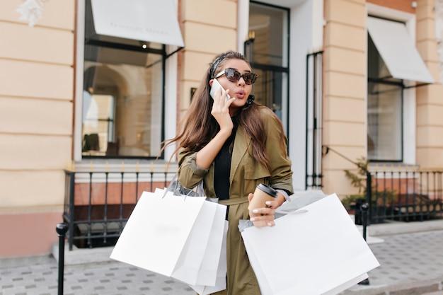 Überraschte brünette dame, die kaffee und taschen vom laden neben boutique hält