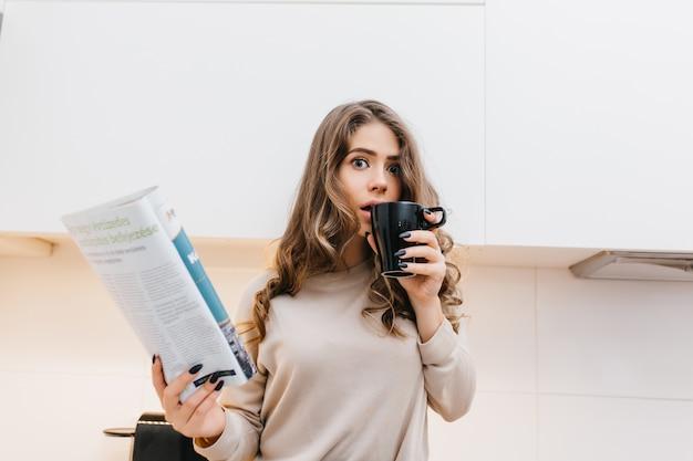 Überraschte brünette frau, die kaffee beim lesen des magazins am morgen trinkt