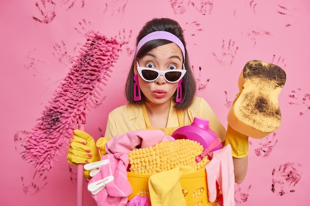Überraschte brünette hausfrau schaut schockiert auf die kamera, wischt staub ab und reinigt den boden mit mopp, der damit beschäftigt ist, hausarbeiten zu erledigen, posen gegen rosa wand mit schmutzigen handabdrücken