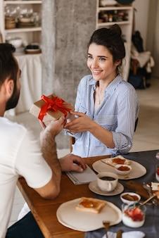 Überraschte brünette paar mann und frau beim frühstück in der wohnung beim sitzen am tisch mit geschenkbox