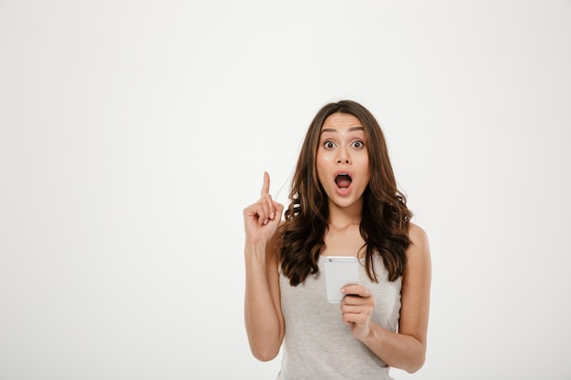 Überraschte brunettefrau, die smartphone hält und idee beim betrachten der kamera über grau hat