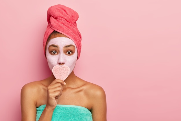 Überraschte dame bedeckt den mund mit einem herzförmigen schwamm, entfernt make-up, trägt eine tonmaske auf das gesicht auf, um jung auszusehen, trägt ein eingewickeltes handtuch auf dem kopf
