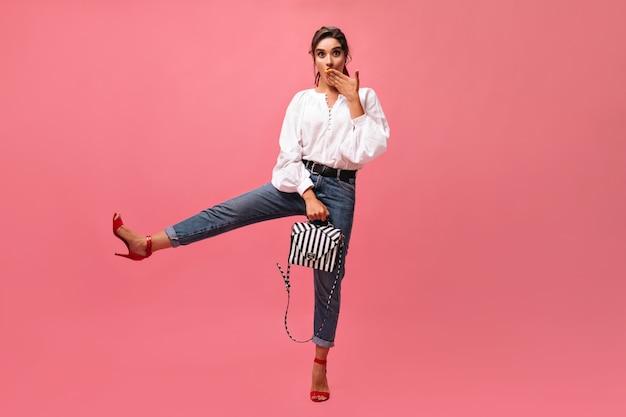 Überraschte dame hebt bein und posiert mit stilvoller handtasche auf rosa hintergrund. lustiges mädchen in der langarmbluse und in den roten hohen absätzen schaut in die kamera. .