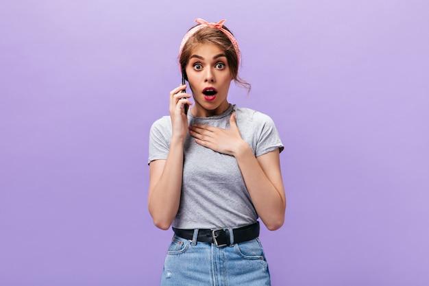 Überraschte dame im grauen outfit, die am telefon plaudert. trendy coole frau in rosa bandana und jeansrock mit schwarzem gürtel, der in die kamera schaut.