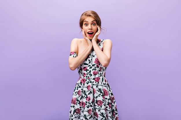 Überraschte dame im kleid mit blumendruck schaut in die kamera. schöne frau in den modischen kleidern, die auf lila hintergrund aufwerfen.