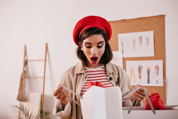 Überraschte dame in roter baskenmütze schaut in einkaufstasche. junge frau mit dunklem haar mit hellem lippenstift in gestreiften stilvollen kleidern, die auf kamera aufwerfen.