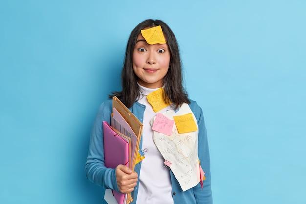Überraschte dunkelhaarige junge asiatische frau, die im büro arbeitet, trägt papiere mit schriftlichen summen, die auf kleidung geklebt werden, hält ordner, die im lässigen pullover gekleidet sind.