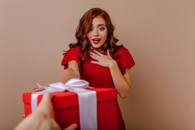 Überraschte elegante frau, die neujahrsgeschenk betrachtet. innenporträt des glamourösen mädchens, das weihnachtszeit genießt.