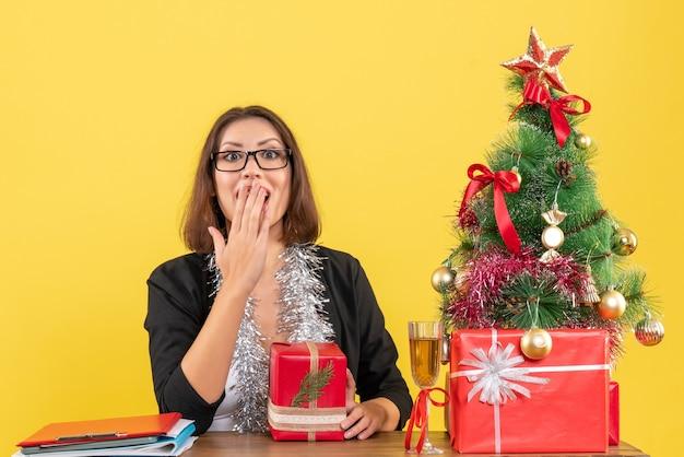 Überraschte emotionale geschäftsdame im anzug mit brille, die ihr geschenk hält und an einem tisch mit einem weihnachtsbaum darauf im büro sitzt
