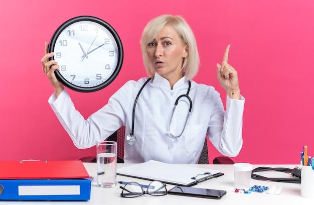 Überraschte erwachsene ärztin in medizinischer robe mit stethoskop, die am schreibtisch mit bürowerkzeugen sitzt, die uhr hält und auf rosa wand mit kopienraum isoliert nach oben zeigt