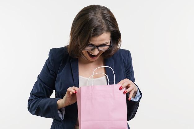 Überraschte erwachsene frau, die einkaufstasche schaut