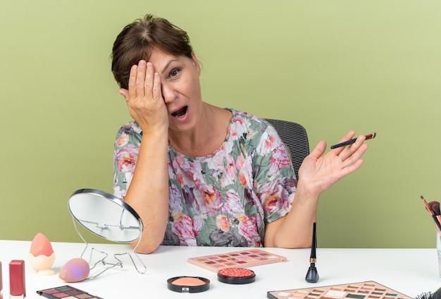 Überraschte erwachsene kaukasische frau, die am tisch mit make-up-tools sitzt, die hand auf ihr auge legt und make-up-pinsel hält