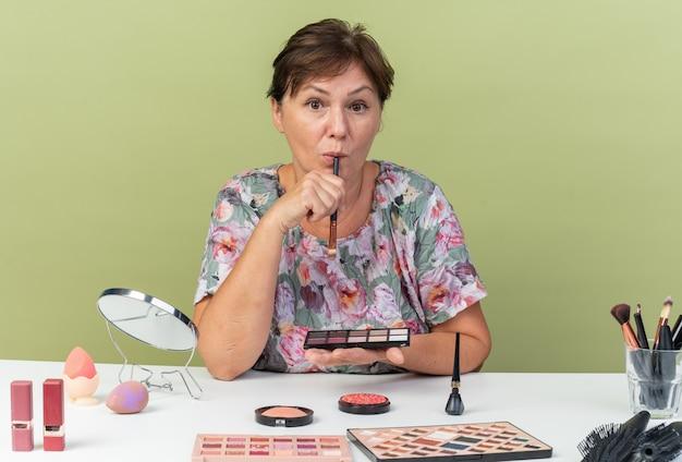 Überraschte erwachsene kaukasische frau, die am tisch mit make-up-tools sitzt und lidschatten-palette und make-up-pinsel hält