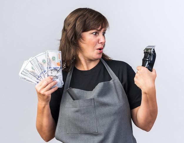 Überraschte erwachsene kaukasische friseurin in uniform, die geld hält und haarschneidemaschine isoliert auf weißer wand mit kopierraum betrachtet