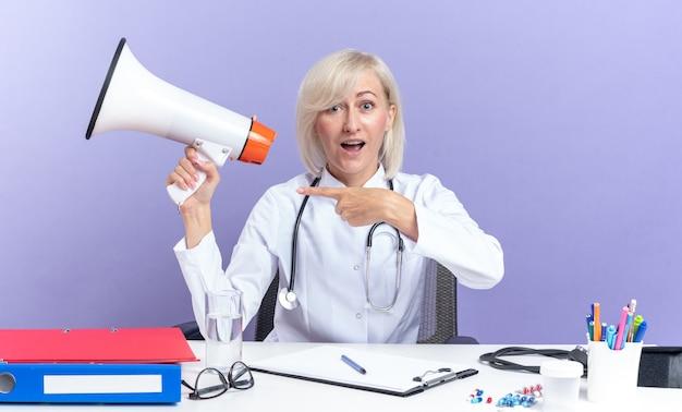 Überraschte erwachsene slawische ärztin in medizinischer robe mit stethoskop, die am schreibtisch mit bürowerkzeugen sitzt und auf lautsprecher zeigt, die auf violettem hintergrund mit kopienraum isoliert sind