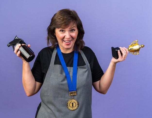 Überraschte erwachsene weibliche friseurin in uniform mit goldener medaille um den hals, die haarschneidemaschine und siegerpokal isoliert auf lila wand mit kopierraum hält