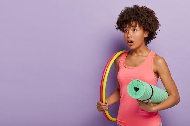 Überraschte ethnische frau mit lockiger frisur, trägt hula hoop, hat training zum abnehmen, führt einen gesunden lebensstil, trägt matte, trägt lässige rosa weste