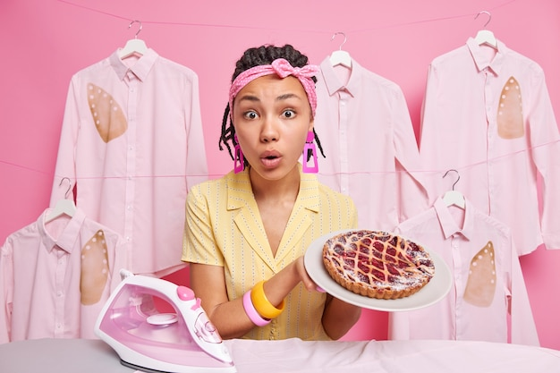 Überraschte ethnische hausfrau hält gebackenen appetitlichen kuchen auf dem teller, der zu hause bügelt und kocht, trägt stirnband-haushaltskleidung gegen gebügelte verbrannte hemden, die am seil hängen.