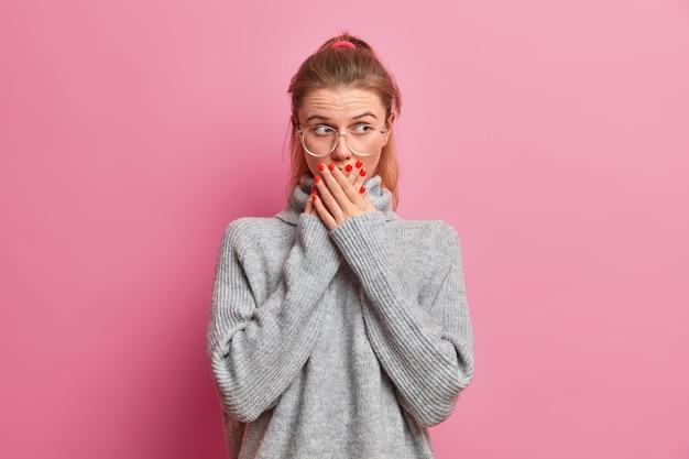 Überraschte europäerin hat einen verblüfften gesichtsausdruck, steht sprachlos, bedeckt den mund, zeigt rote maniküre, gekleidet in einen grauen, losen pullover