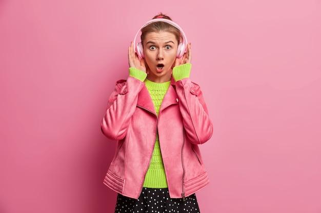 Überraschte europäische frau hört großartige songs in kopfhörern, schockiert von zu lauter lautstärke, wählt songs in der wiedergabeliste aus, entscheidet, was sie hören soll, trägt stilvolle kleidung