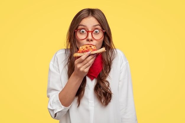 Überraschte europäische modische frau hat ein stück pizza, sieht in übergroßem hemd gekleidet aus, überrascht von sehr gutem geschmack, isoliert über gelber wand. menschen und fast-food-konzept