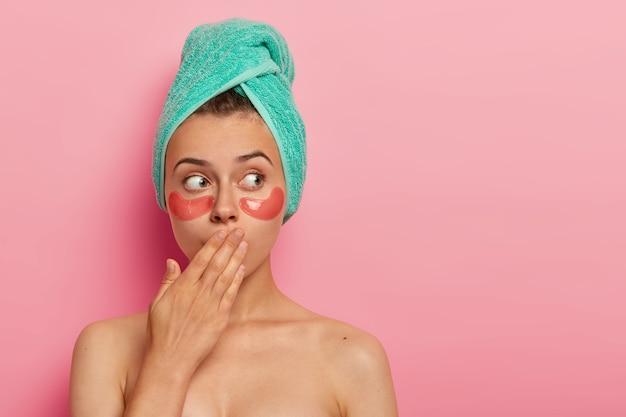Überraschte frau bedeckt den mund, trägt kosmetische flecken unter den augen. gesichtsbehandlung und schönheitskonzept