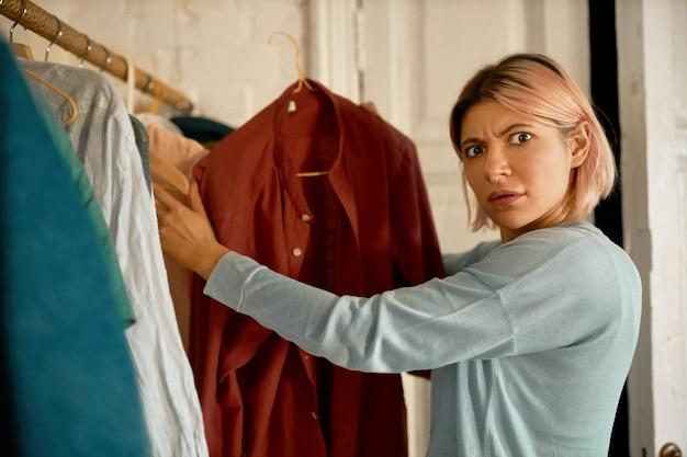 Überraschte frau bekommt kleidung vom waschmaschinenzentrum.