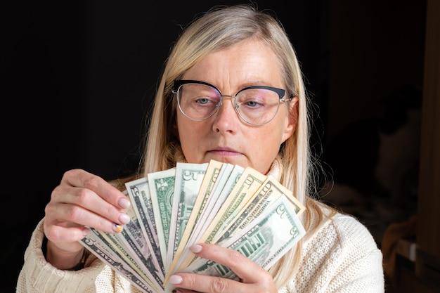 Überraschte frau, die an einem tisch sitzt und dollarnoten betrachtet und das verdiente finanzielle wohlfahrtskonzept genießt