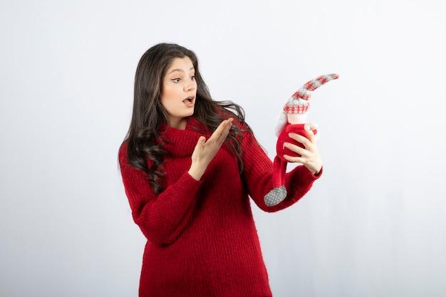 Überraschte frau, die an einem weihnachtsmann-plüschtier zeigt..
