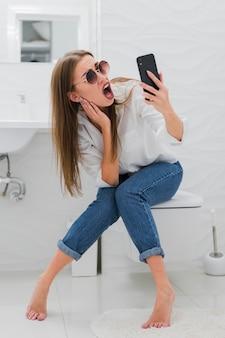 Überraschte frau, die auf ihr telefon schaut