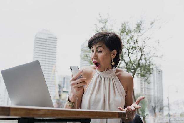 Überraschte frau, die ein telefon auf städtischem hintergrund hält