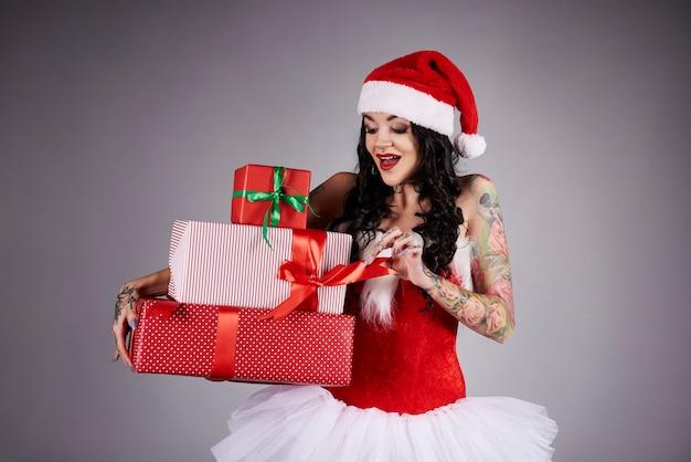 Überraschte frau, die ein weihnachtsgeschenk öffnet