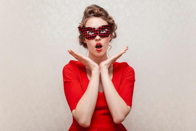 Überraschte frau, die eine karnevalsmaske trägt