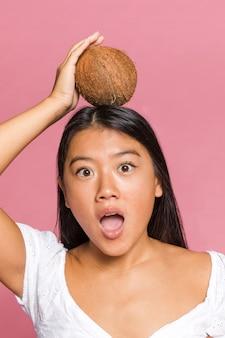 Überraschte frau, die eine kokosnuss auf ihrem kopf hat