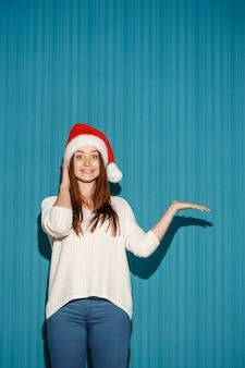Überraschte frau, die eine weihnachtsmütze trägt, die rechts auf blauem hintergrund zeigt