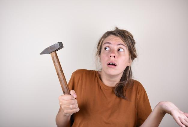 Überraschte frau, die einen hammer in ihren händen hält