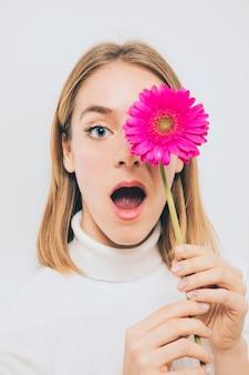 Überraschte frau, die gerberablume am gesicht hält