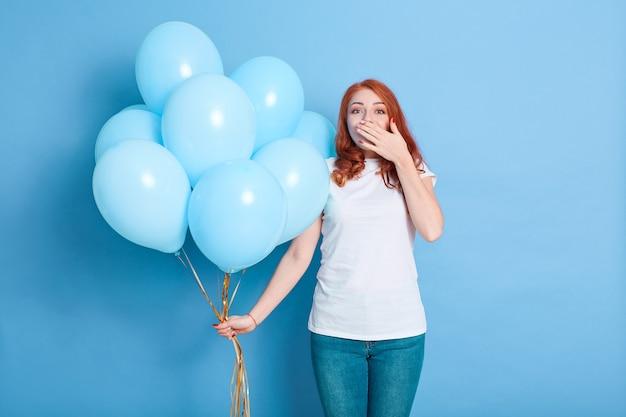 Überraschte frau, die luftballons hält und mund mit hand bedeckt