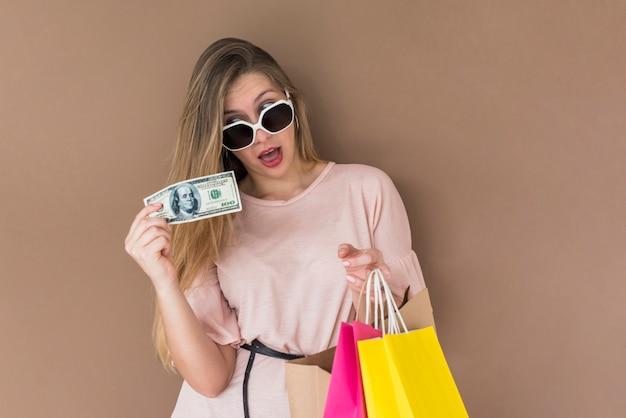 Überraschte frau, die mit einkaufstaschen und geld steht