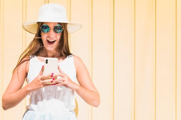 Überraschte frau, die nahe hölzerner wand mit smartphone steht