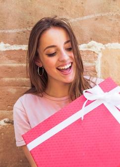 Überraschte frau, die rote geschenkbox betrachtet