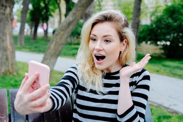 Überraschte frau, die selfie mit smartphone nimmt, während draußen auf einer bank im gestreiften oberteil sitzt